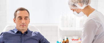 Badania krwi - pielęgniarka pobierająca od pacjenta próbkę krwi